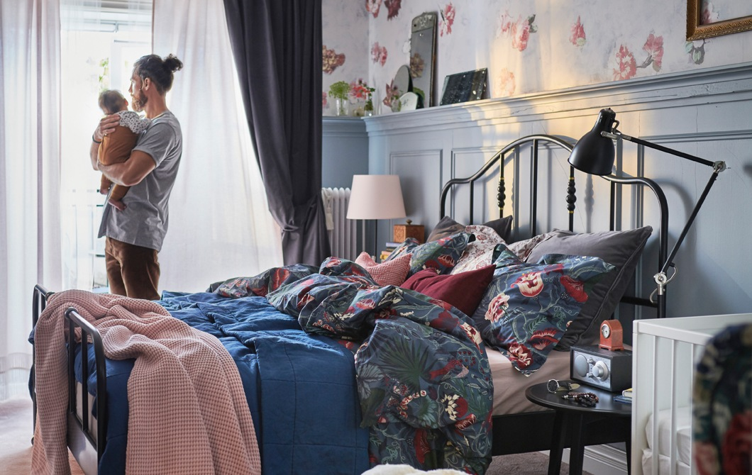 A man stands holding a baby in a bedroom with patterned floral bedding and layers of curtains at the window.