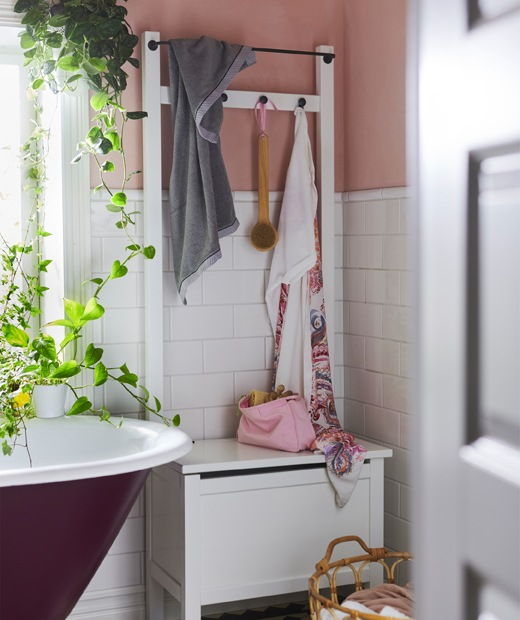 A storage bench with hooks and a rail next to a bath and plants.