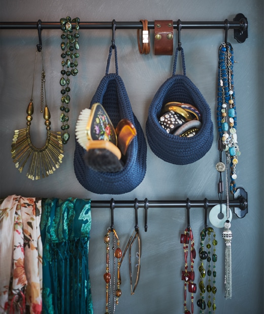 Jewellery and accessories hanging from rails on a blue wall.