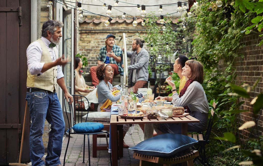 People sitting around a wooden table in a backyard area with brick walls and plants.