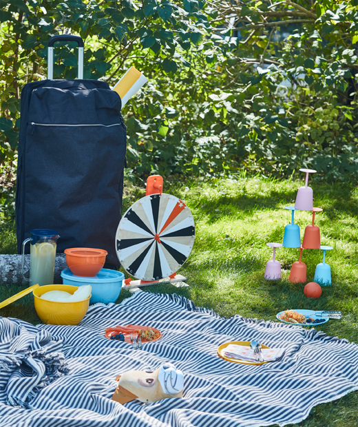 A picnic in the grass with tableware, games and a big blanket brought with a blue FÖRENKLA XL duffle bag on wheels.