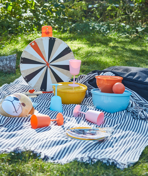 A picnic in the grass with plastic tableware and wine glasses in mixed colours.