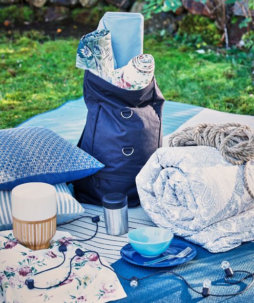 A summer picnic with cushions, blankets and battery charged LED lighting like MULLBACKA table lamp.