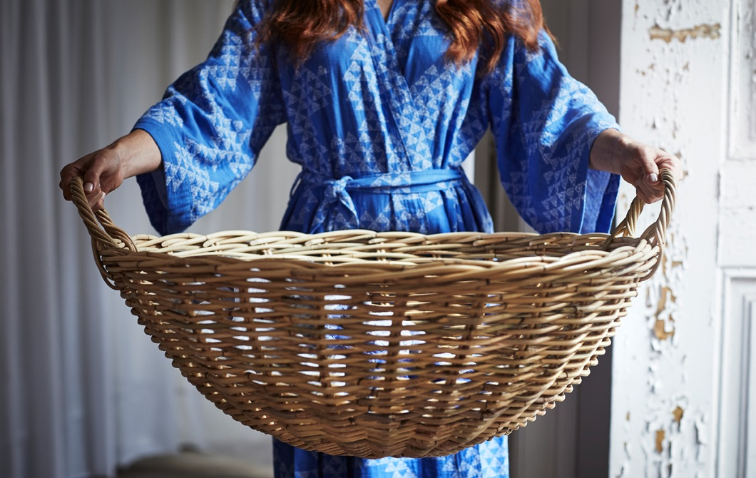A person wearing a blue patterned kimono holds a large round rattan basket.