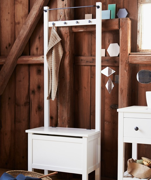 A tall white storage bench with rail and hooks at the top and a seat compartment.