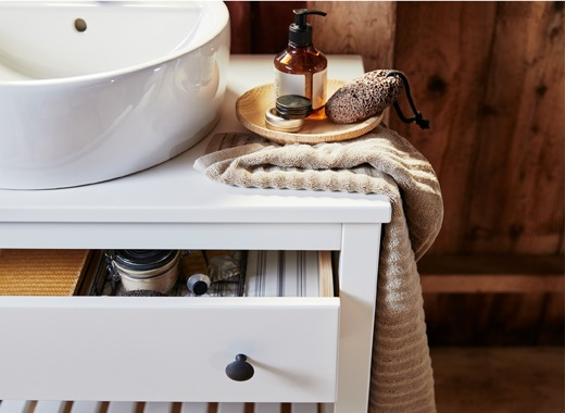 A close-up of a sink, towel and soaps on a white vanity unit with the drawer open.