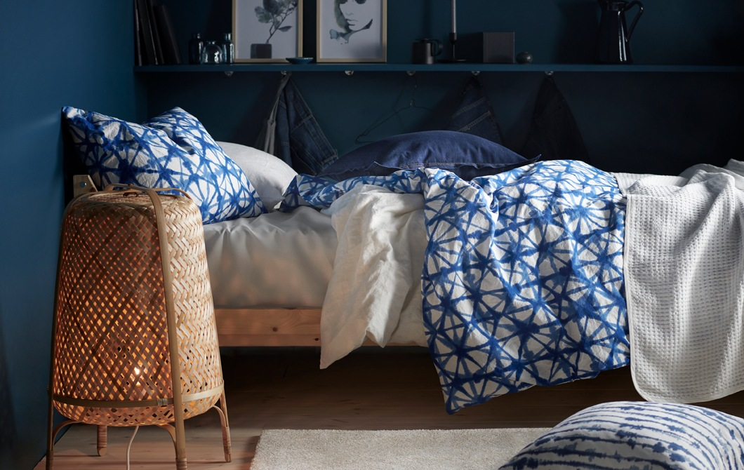A bed with blue and white patterned bedding and a bamboo floor lamp in a room with dark blue walls.