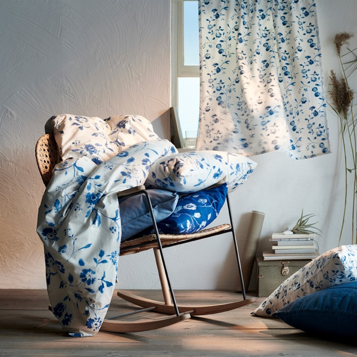 Blue and white floral textiles on a rattan rocking chair, and a floral curtain across a window behind.