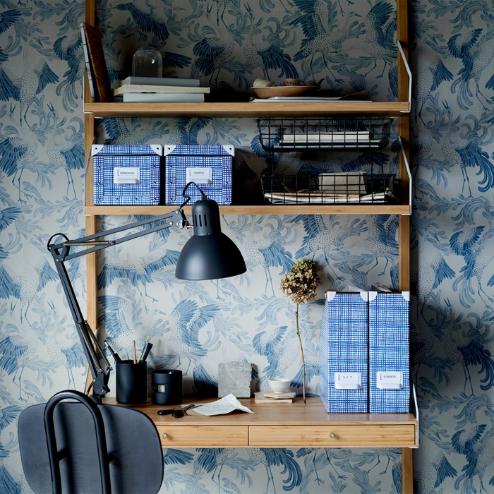 Blue patterned boxes and files on a wooden desk with built-in shelves and a black work lamp.