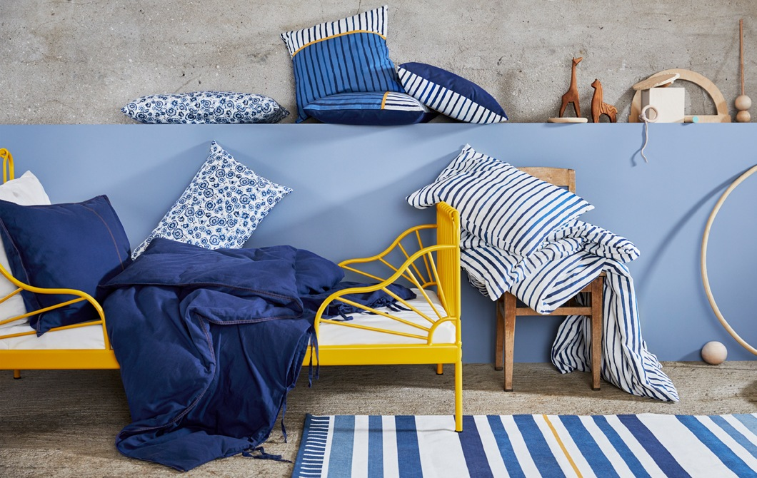 A yellow bed frame with blue and white bedding in floral and striped prints, and cushions and wooden toys on a blue wall.