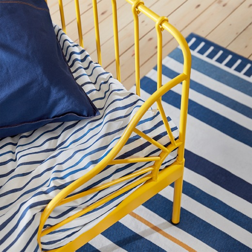 A close-up of the corner of a yellow bed frame with blue and white striped bedding and rug.