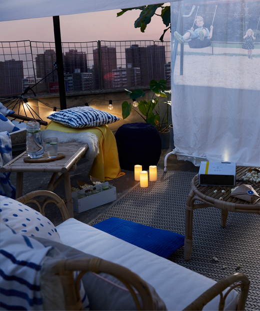 A coffee table with popcorn grouped with pouffes, outdoor armchairs and a hammock in front of a film screen on a rooftop.