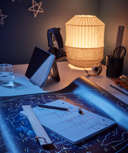 Workspace-style desk with star map and calendar, lit acorn-shaped table lamp and filled tablet stand.