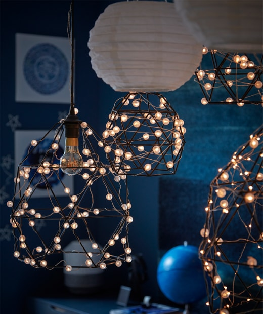 A moonlit, dark blue room section with astronomy decorations and lighting formed by SNÖYRA-wrapped BRUNSTA lamp shades.
