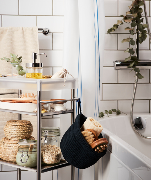 A trolley loaded with spa-style accessories, rolled in place next to a bathtub; a eucalyptus twig hangs from the shower head.