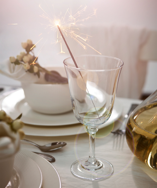 Individual place at extravagantly set table, white tableware and flowers, fronted by a wine glass holding a lit sparkler.