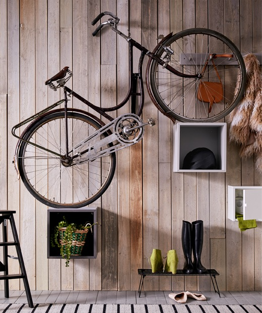 A plain bicycle placed with its wheels on EKET cabinets set at different heights, giving the bike a steep-uphill tilt.