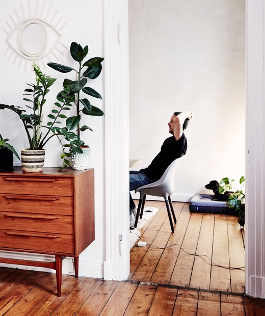 André sitting back in a chair through a doorway, with wooden floorboards and vintage furniture.