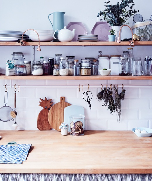 Storage jars and serveware on two wooden shelves above a wooden kitchen worktop.