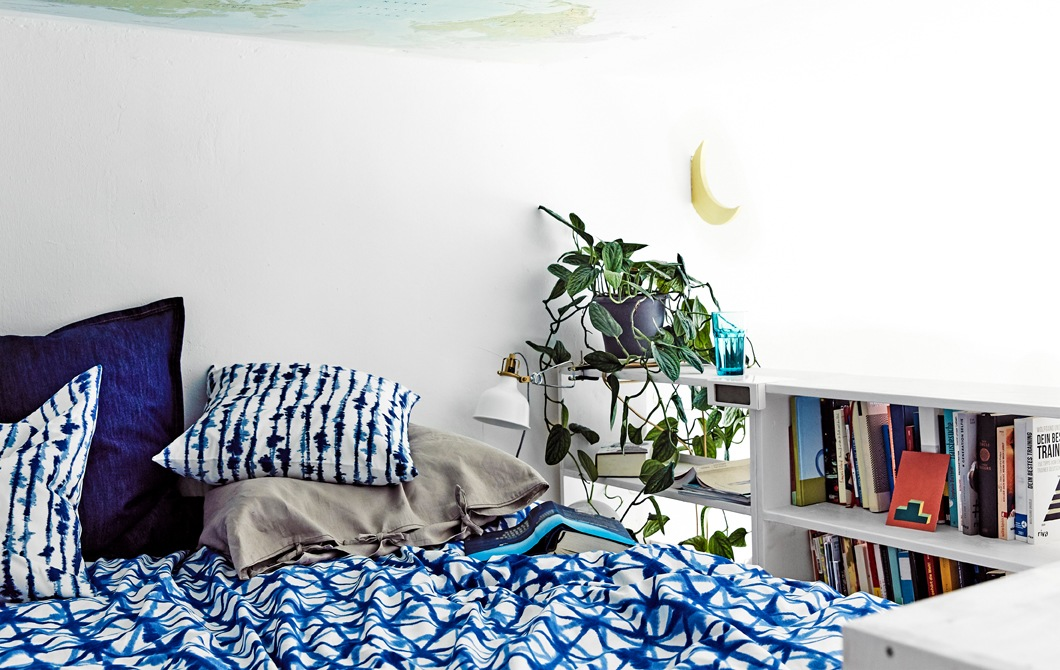 A bed with patterned blue bedding and a bookshelf along the side.