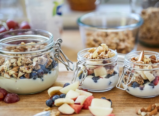 Three glass jars filled with yoghurt, granola, fresh fruit and nuts on a wooden countertop.