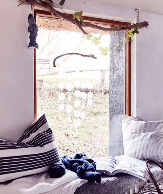 A window seat with striped cushions and throws.