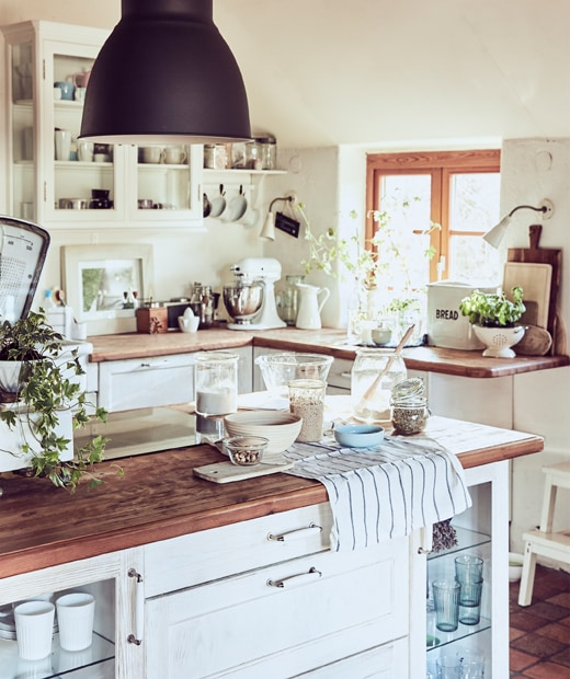 A white, rustic-style kitchen with wooden worktops a and baking equipment on a kitchen island.