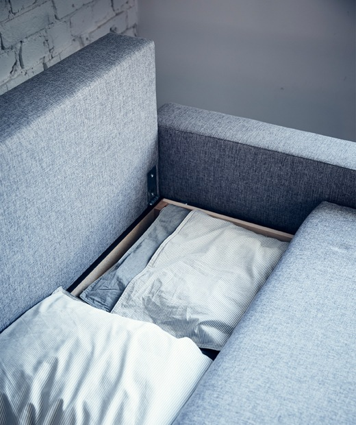 Bedding stored inside a grey sofabed.