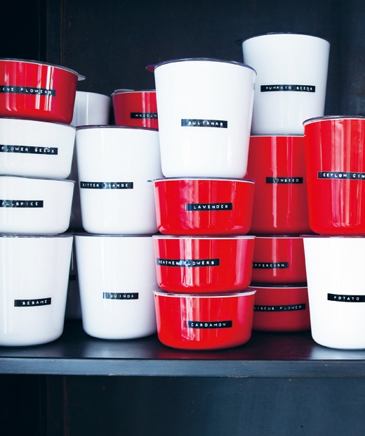 Stacks of red and white pots labelled with dry ingredients.