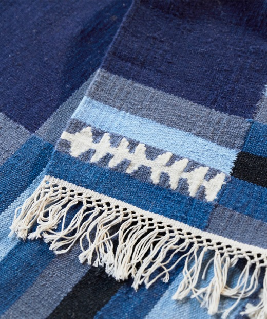 A blue patterned rug with fringed edging.