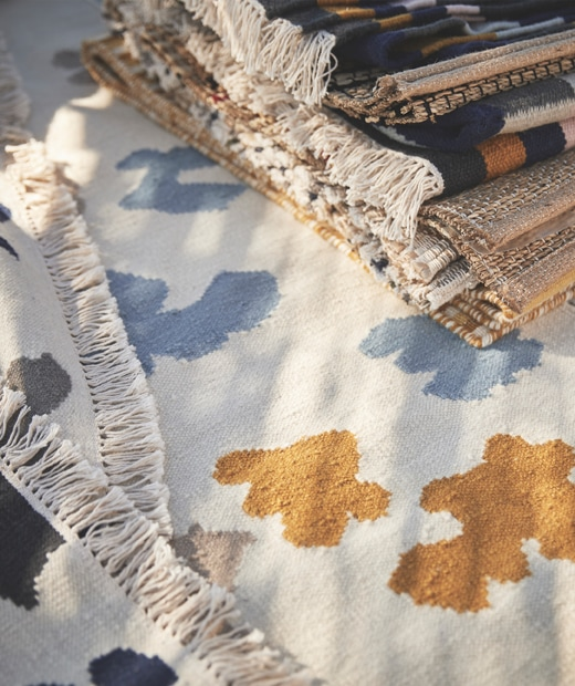 A pile of rugs on a white rug with blue and yellow pattern.