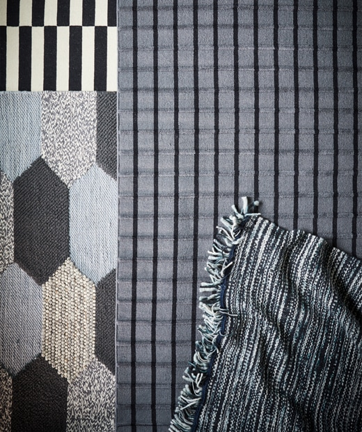 Four different rugs with monochrome patterns and stripes.
