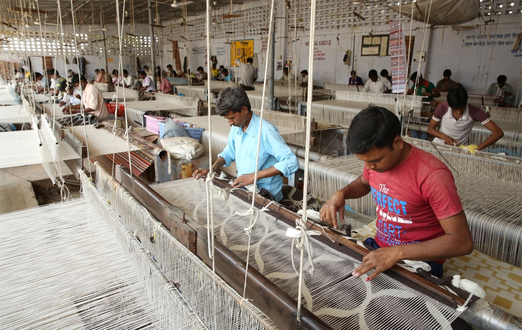 A large workshop with people weaving wool on looms.