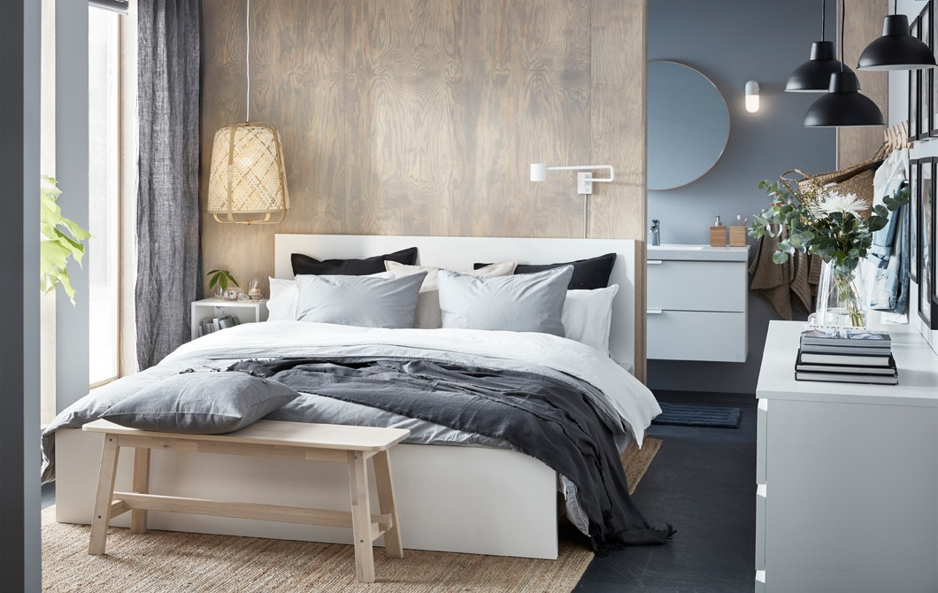 A bedroom with a neutral colour scheme, double bed, wooden bench and wicker lamp.