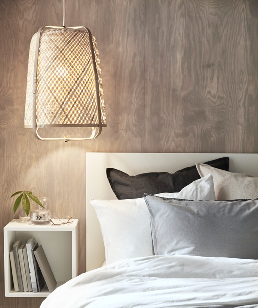A bamboo lamp hanging low over a bed and a square storage unit on the wooden wall behind.