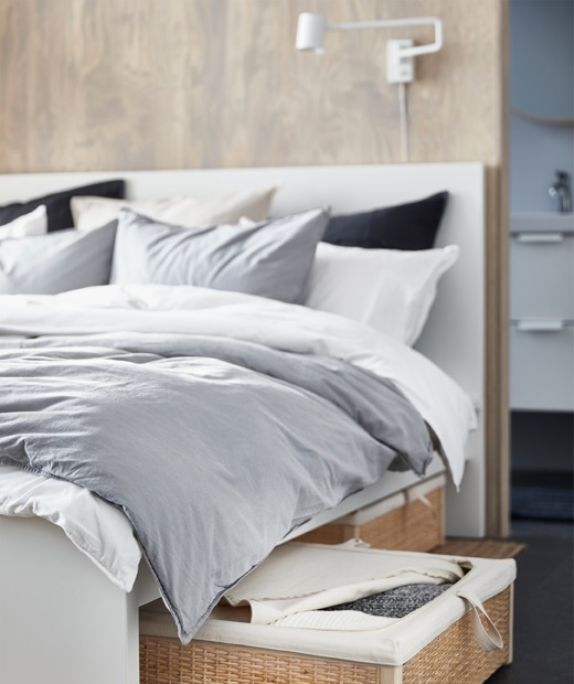 A bed with grey and white bedding and a rattan storage box underneath.