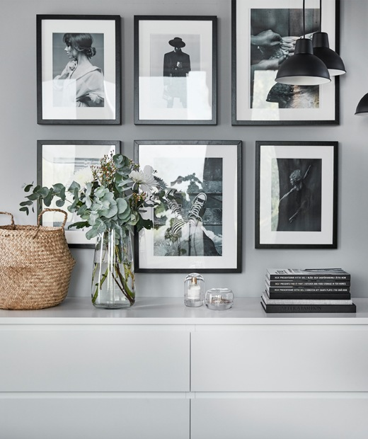 A gallery of black and white pictures on a wall above two white chests of drawers.