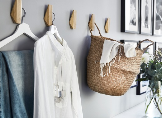 Clothes and a basket hanging on wooden hooks on a grey wall.