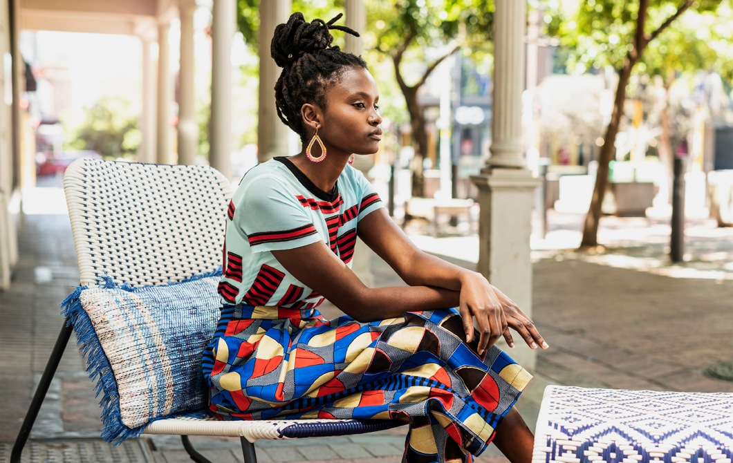 A woman in colourful clothes sitting on a rocking chair outdoors.