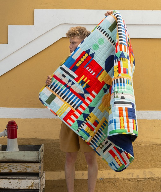 A man holds up a blanket with multicolour pattern in front of a yellow wall.