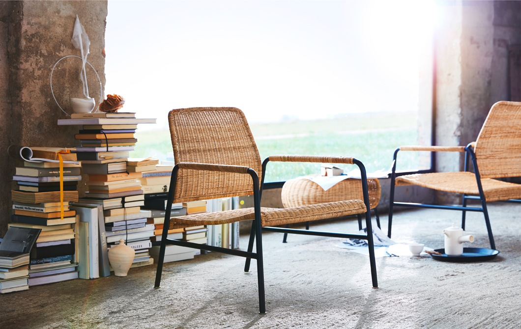 Rattan and metal chairs, and a footstool in front of piles of books and a large window.