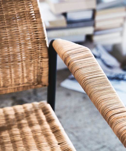 The arm and seat of a rattan armchair with metal frame.