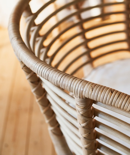 The curved frame of a rattan armchair.