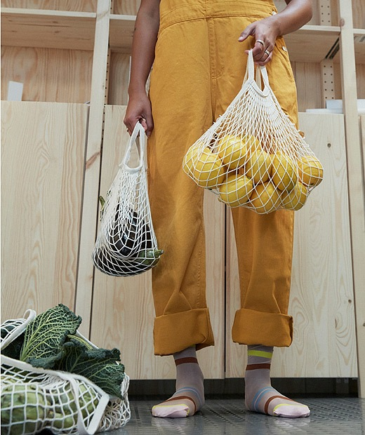 A girl wearing a yellow jumpsuit holding bags of fruit and vegetables.