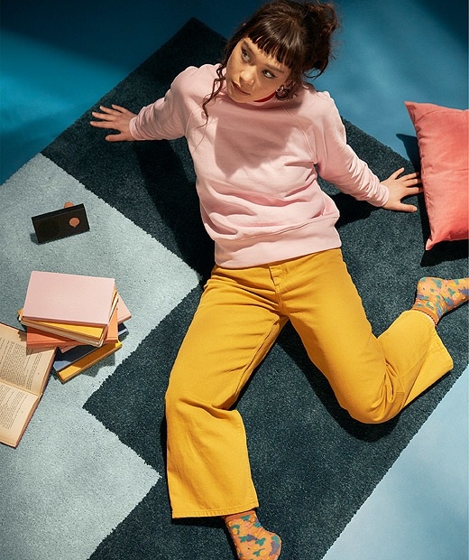 A student sitting on a rug in a relaxed manner surrounded by books and a wireless speaker.