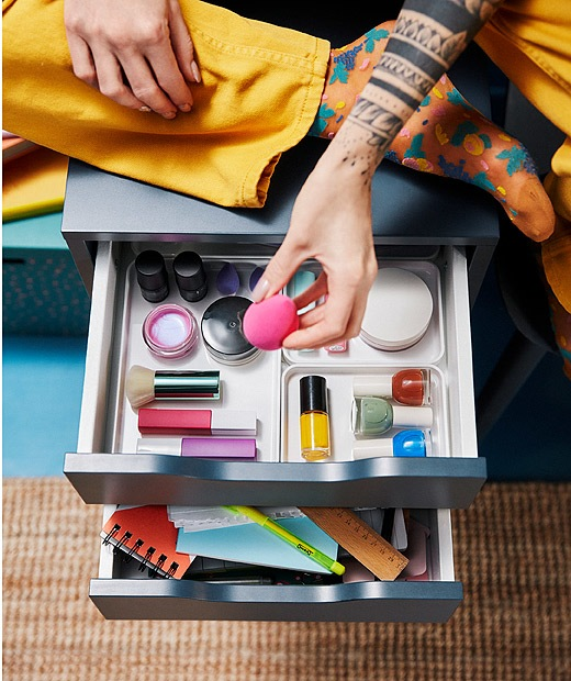A girl with tattoos sitting on a chest of drawers playing around with beauty accessories.