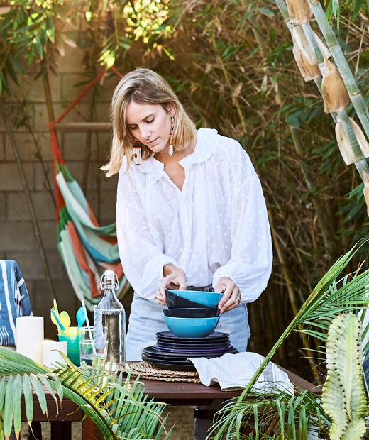 Chloé stacking bowls on a wooden table in the garden.