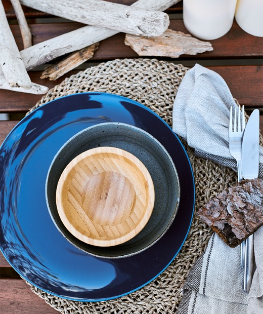 A stack of dark blue and wooden bowls on a woven placemat and driftwood on a wooden table.