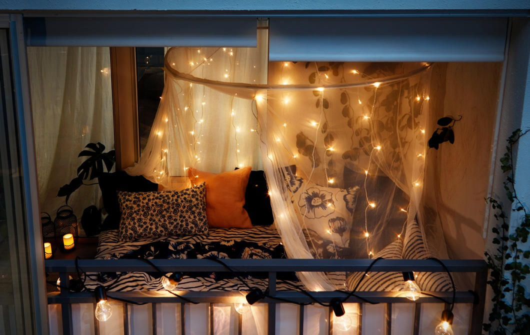 Night-time view, from the outside looking in, of an enclosed balcony decked out in full bedroom manner, mood lights and all.