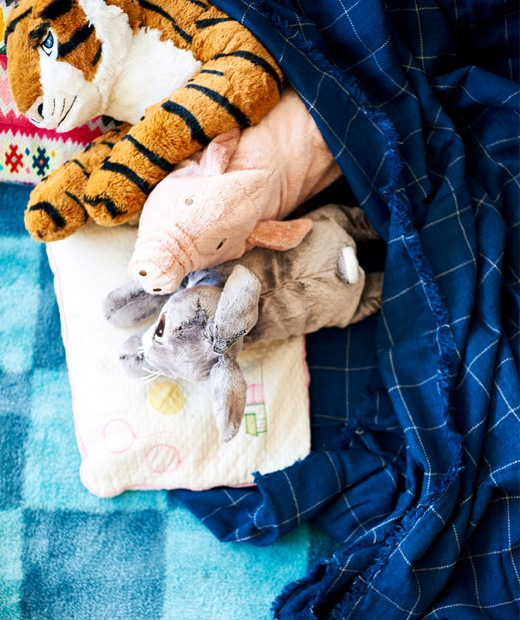 A collection of children's soft toys under a blue throw on a blue rug.